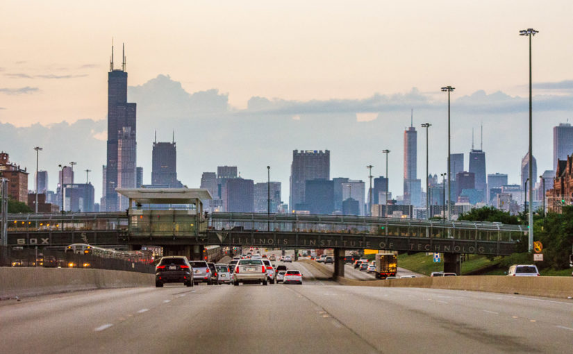 Cars drive north into the Downtown Chicago skyline on the Dan Ryan Expressway at sunset
