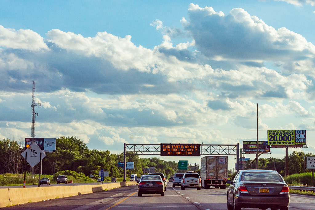 Traffic flows under partly cloudy skies on a Friday evening along I-80/94 in Lake Station, Indiana near Chicago. An electronic sign warns of slow traffic ahead.