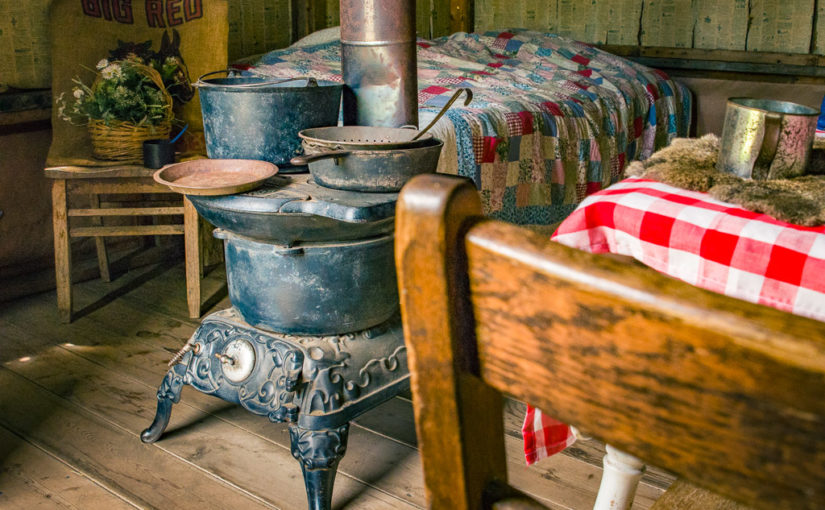A red-checkered tablecloth, a potbelly stove, and a quilted bed sit inside a sample shanty similar to what many Great Plains homesteaders lived in at the Ingalls Homestead in De Smet, South Dakota.