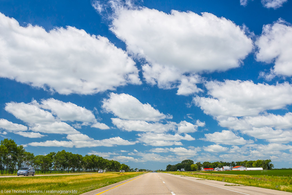 Cumulus clouds stretch across the sky over I-90 and prairie farmlands near Blue Earth, Minnesota.