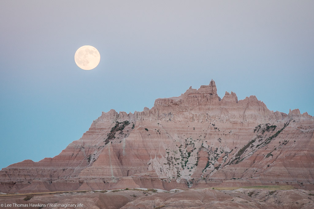 A full moon rises over The Castle at sunset from the White River Valley Overlook in Badlands National Park in South Dakota.