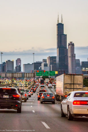 The Sears Tower stands prominently in Downtown Chicago as cars slow down for a traffic jam on the Dan Ryan Expressway.
