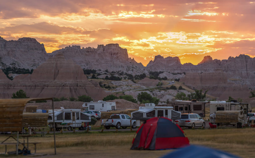 The sun rises over the Badlands Wall and Cedar Pass Campground in Badlands National Park in South Dakota.