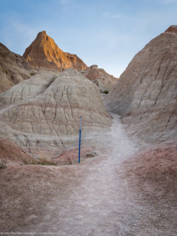 Looking up the Saddle Pass Trail in Badlands National Park. Blue markers help to identify the trail amid the indistinct terrain.