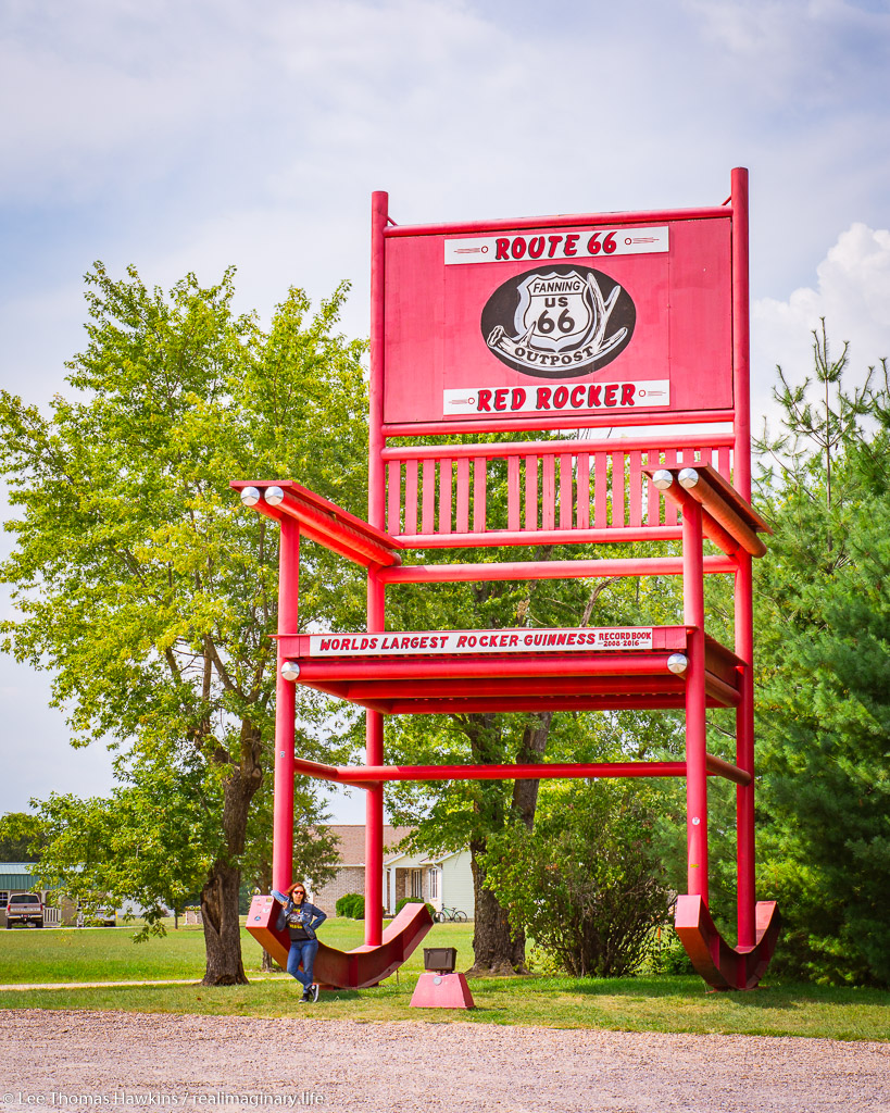 Becky stands under The Red Rocker in Fanning, Missouri, the world's largest rocking chair from 2008 to 2016.