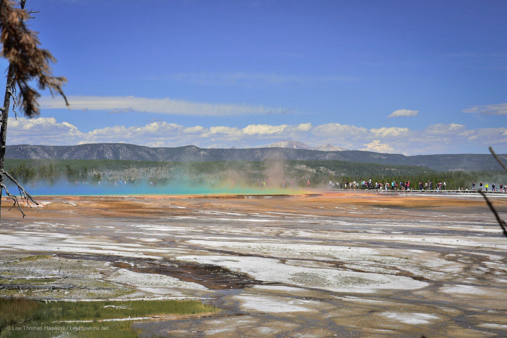 Colored steam rises from a hot spring in a barren landscape surrounded by picturesque mountains.