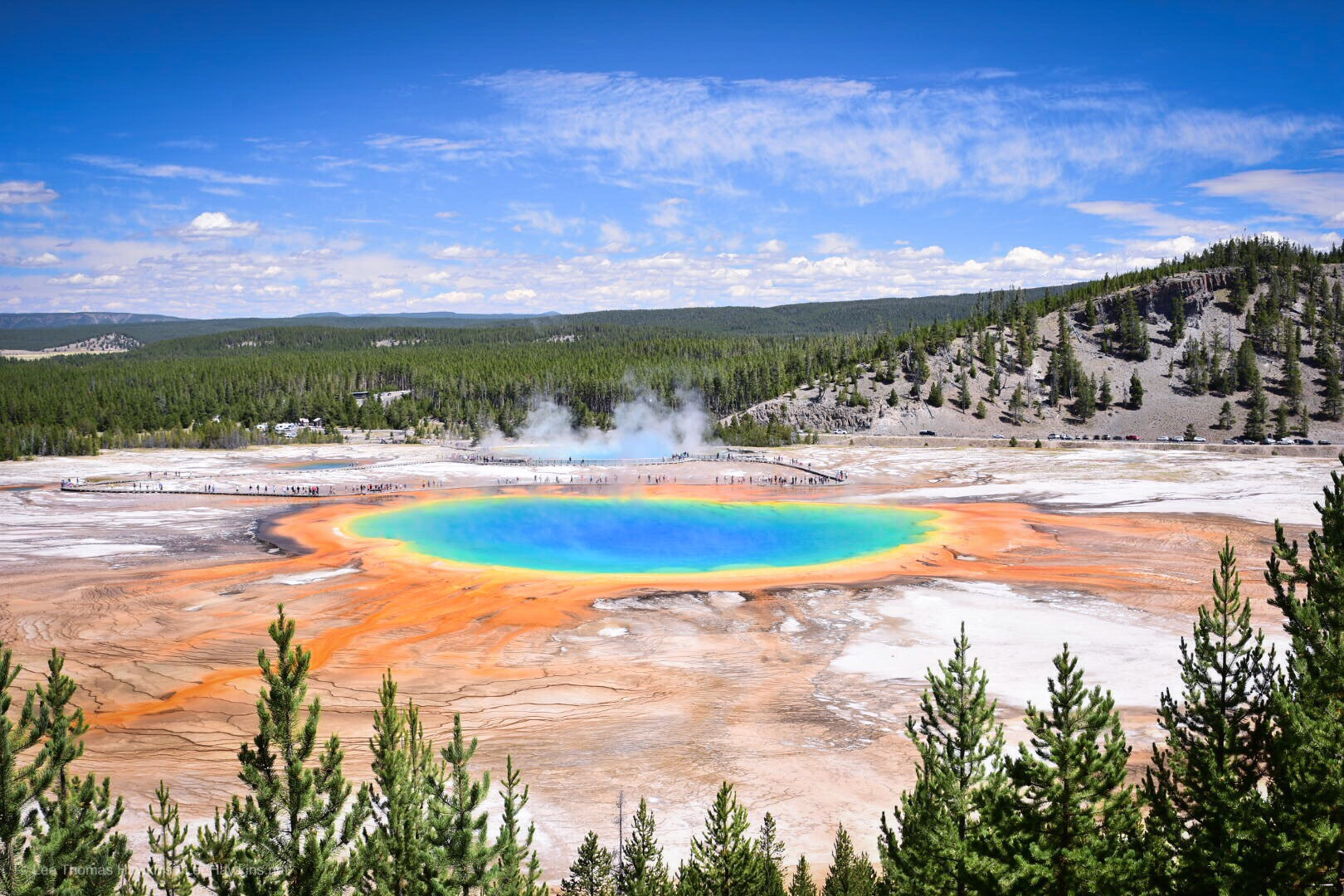 A gigantic hot spring with deep blue and green colors in the center is surrounded by yellow, orange, and red colors on the fringes.