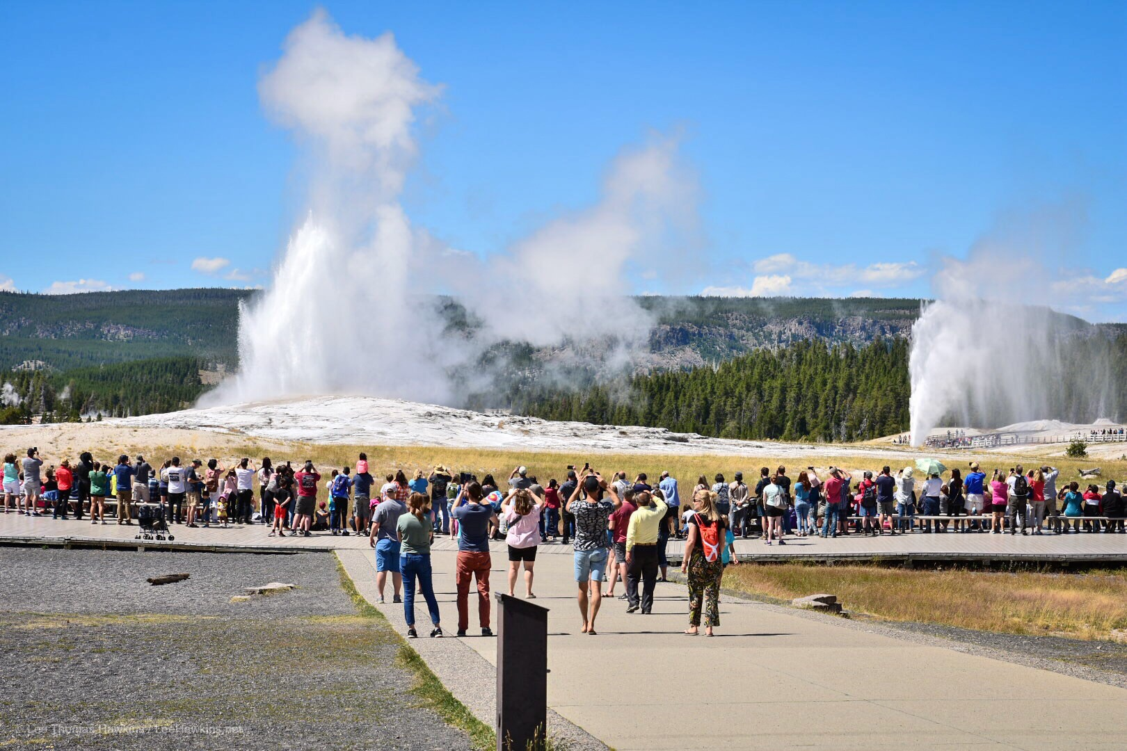 Two large geysers erupt simultaneously, one in the foreground surrounded by a crowd of spectators, and the other in the distance.