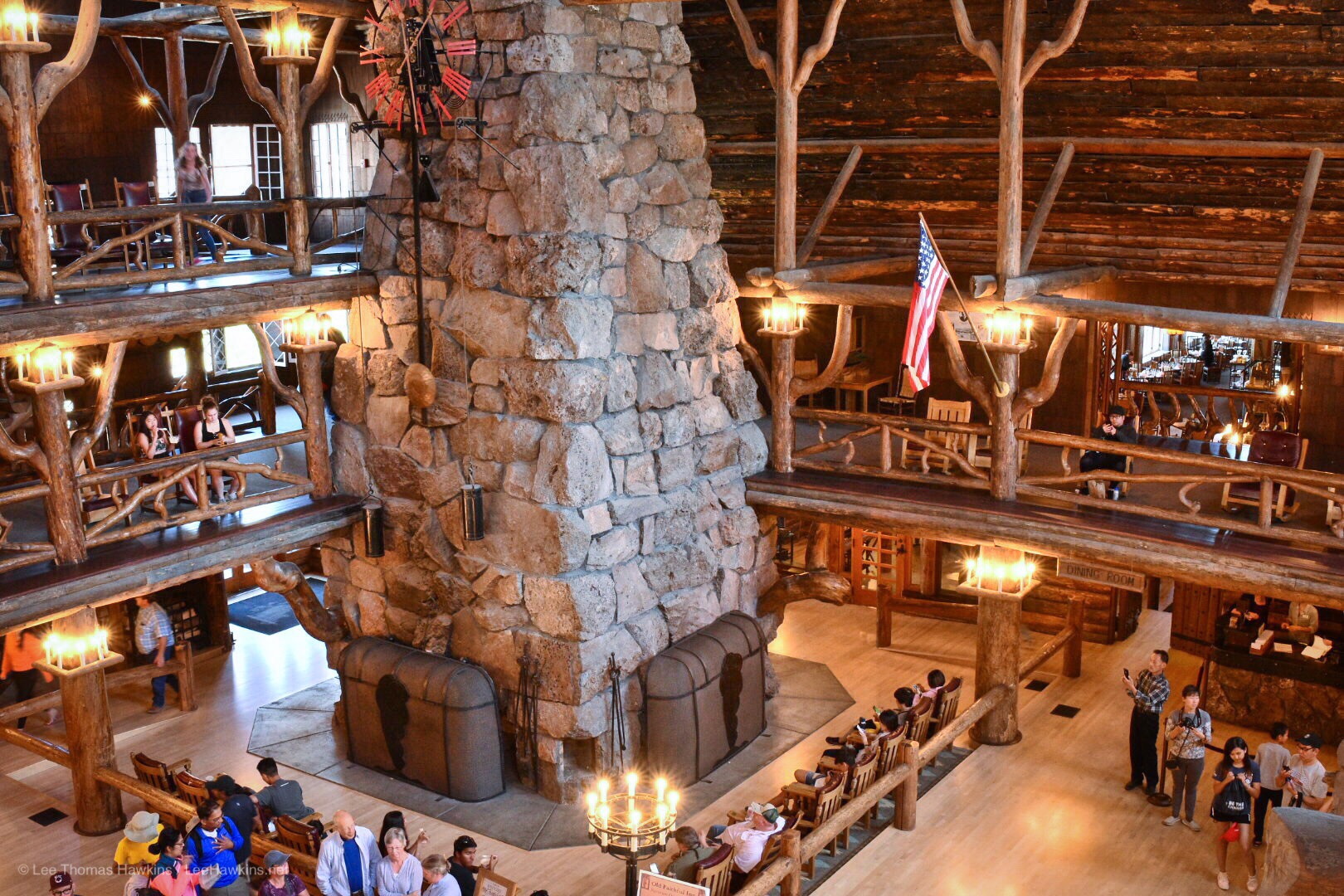 The rustic wood atrium of a hotel lobby rises multiple levels around a stone chimney surrounded by people.