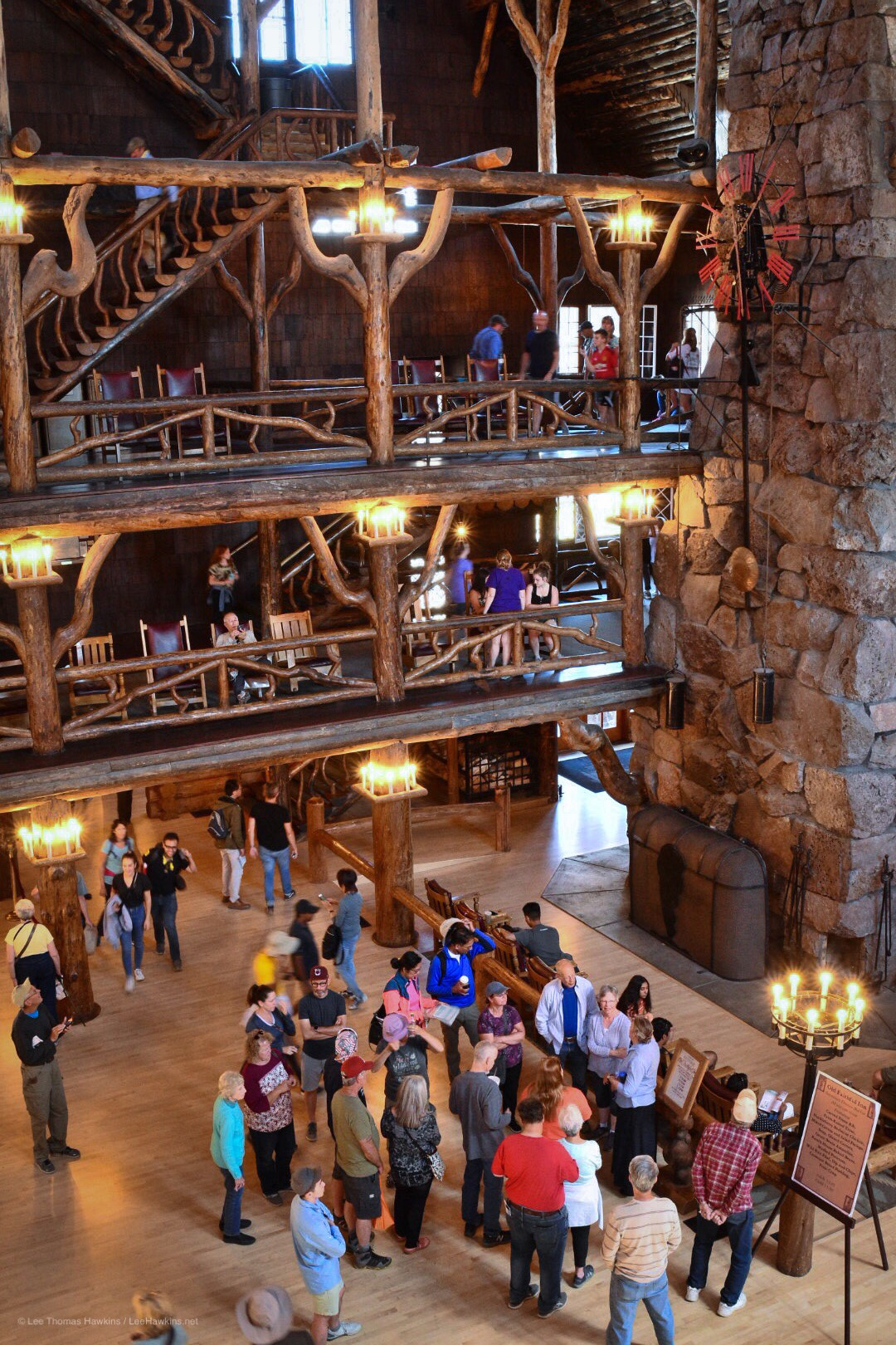 The rustic wood atrium of a hotel lobby with grand staircases rises multiple levels around a stone chimney surrounded by people.