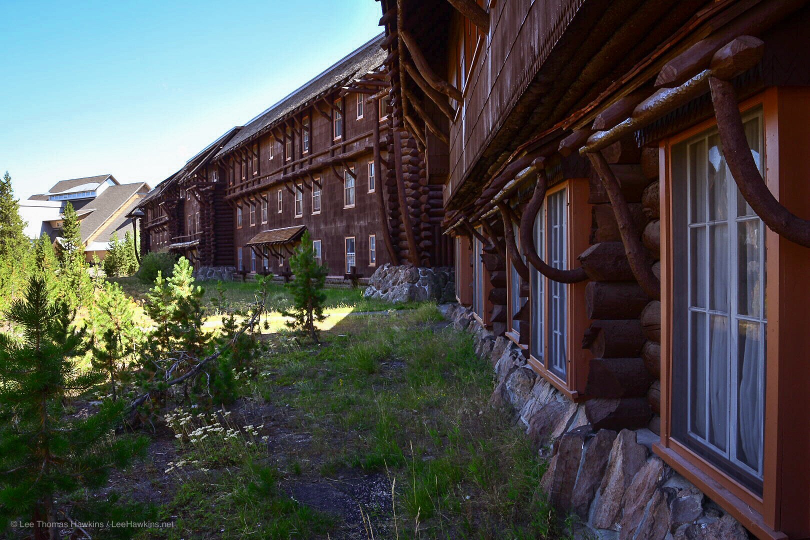 Bent logs form the many intricate details of a rustic wooden hotel building.